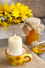 Jar of honey on wooden table, bouquet of sunflowers in the backg