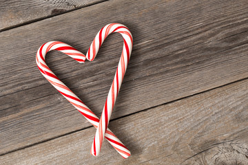 Christmas candy canes on wooden surface .