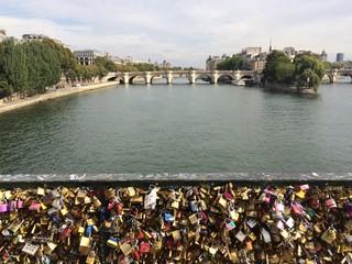 Locks attached to a bridge over river seine in Paris