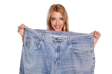 skinny beautiful blonde holding her old big pants