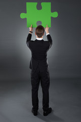 Businessman Holding Green Puzzle Piece