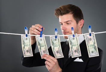 Businessman Drying Dollar Bills On Clothesline