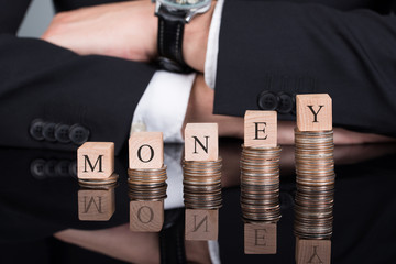Businessman With Money Blocks On Stacked Coins