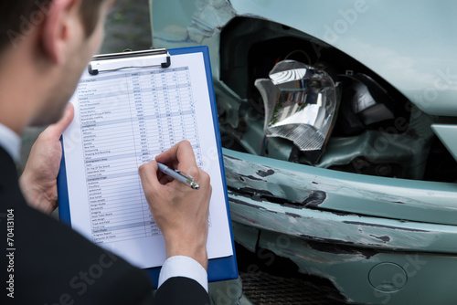 Insurance Agent Examining Car After Accident - 70413104