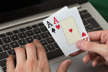 Businessman Holding Cards While Using Laptop