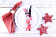 White plates, knife, fork, napkin and Christmas decoration