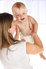 Cute baby boy with mom on light background
