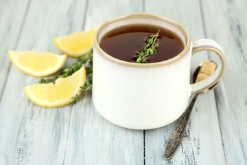 Cup of tasty herbal tea with thyme and lemon on wooden table