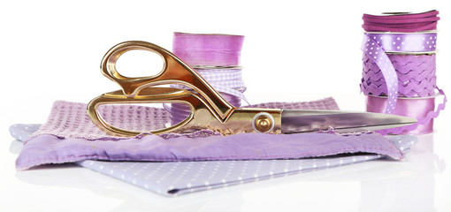 Ribbons with scissors and fabrics isolated on white