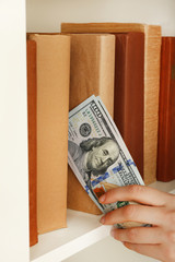 Woman hiding money in book at home