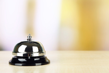 Reception bell on desk, on bright background