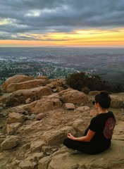 Woman meditating on mountain in lotus position, San Diego, CA