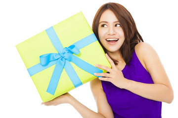 surprised young woman holding a gift box over white background