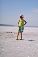 on the shores of the salty shore of the estuary stands a boy in