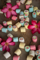 marshmallows and flowers on wooden background
