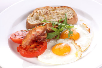 Freid eggs with tomatoes and becon.