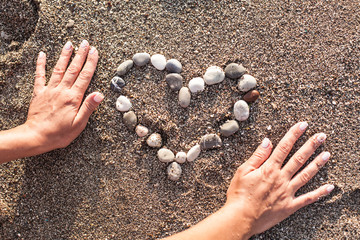 Woman's hands making heart of marine shingles on the sand.