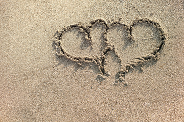 Two hearts written on the sand.