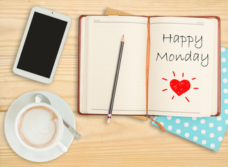 Happy Monday on notebook with pencil, smart phone and coffee cup