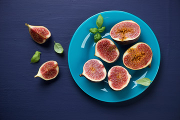 Glass plate with sliced fig fruits, dark blue wooden background