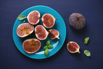 Sliced figs on a glass plate, dark blue wooden surface