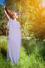 Girl holds himself for loose hair standing in a dress on nature