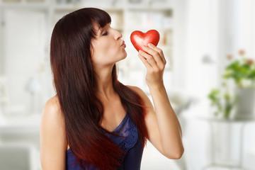 hübsche Frau küsst rotes Herz