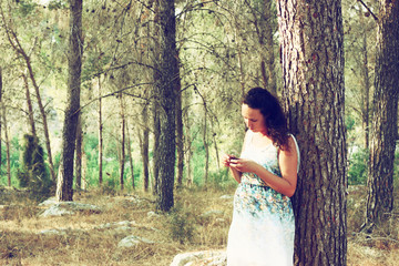 surreal blurred background of young woman stands in forest.