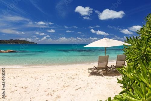 Leinwanddruck Bild Chairs and umbrella on a beautiful tropical beach of Seychelles