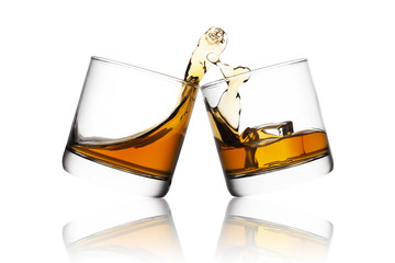 Splash of whisky in two glasses isolated on white background
