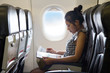 Young woman sits in a chair of the airplane - 70424753