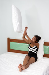 Cheerful woman playful with pillow in bed