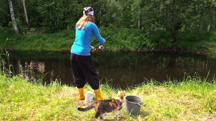 woman fish in pond, cat fawn along feet. Fun free time nature