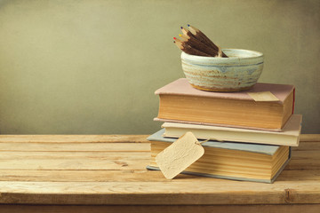 Books and pencils on wooden table in vintage style