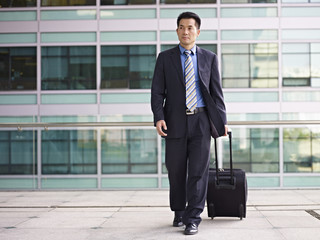 asian business traveler walking with luggage