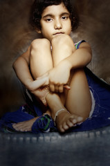 portrait of small girl sitting with folded arms leg