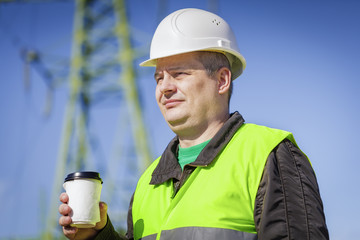 Engineer with coffee near high voltage towe