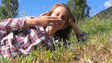 young woman lying in a grass blows a kiss toward the camera