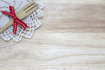 picture of fork with ribbon and doily on wooden background