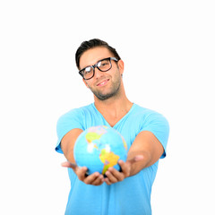 Portrait of young handsome man holding globe in hands against wh