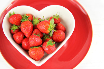 Heart shaped bowl of juicy red strawberries