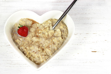 Breakfast Oatmeal or Porridge in a heart shaped bowl. Rustic bac