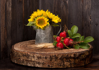 Autumn composition. Sunflower and wild rose on wooden board.