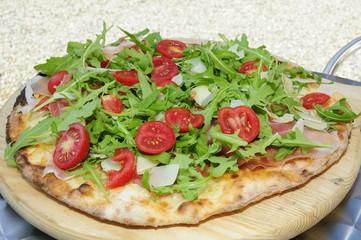 Pizza con pomodorini grana rucola e prosciutto crudo