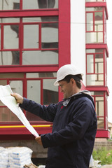 builder in helmet with blueprint on building site
