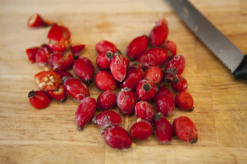 Cut rosehips on chopping board with knife