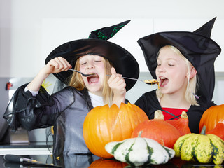 Little witches taste pumpkins in the kitchen