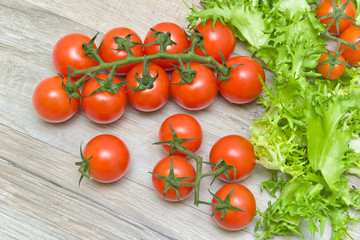 cherry tomatoes and lettuce on a wooden background
