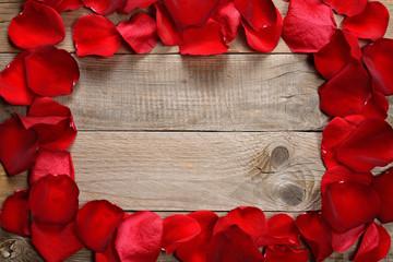 Frame of red rose petals on wooden background