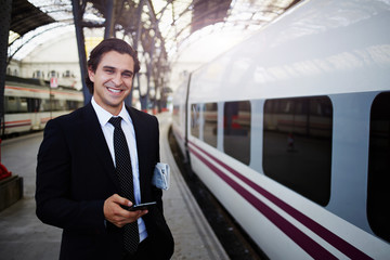 Successful rich businessman smiling holding mobile phone